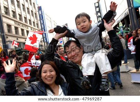 VANCOUVER, BC, CANADA - FEBRUARY 28: Canadian family enjoys festive atmosphere in Vancouver during 2010 Winter Games, February 28, 2010 in Vancouver, BC, Canada - stock photo