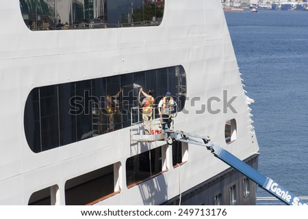 VANCOUVER, CANADA - AUGUST 6, 2005: Two Window Washers cleaning the Windows of a Cruise Ship. The Cruise Ship is docked on Canada Place, the main cruise ship terminal for the region. - stock photo