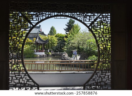 VANCOUVER, CANADA - AUGUST 6, 2005: View through Screen in Dr. Sun Yat-Sen Classical Chinese Garden with Pagoda and Pond in Vancouver, Canada.  - stock photo