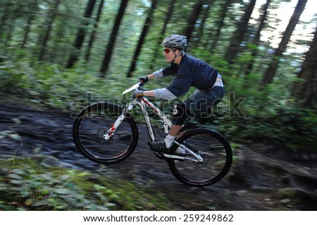 VANCOUVER, CANADA - JUNE 8, 2012: An athlete competes in Adidas Eyeware Chainless Downhill Bicycle Race in the North Shore mountains in North Vancouver, Canada on June 8, 2012.  - stock photo