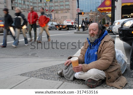 VANCOUVER, CANADA - JUNE 1, 2012: Homeless people, like pictured ones, can be seen almost on every corner of every street in the heart of downtown in Vancouver, Canada, June 1, 2012.