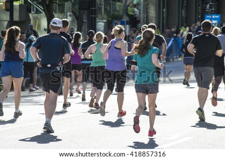 Vancouver, Canada - May 1, 2016: A group of people running in the BMO Vancouver Marathon run up the final hill towards the finish line.