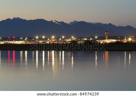 Vancouver International Airport, YVR, at dusk reflecting in the calm waters of the Fraser River. The Coast Mountains rise in the background. British Columbia, Canada. - stock photo