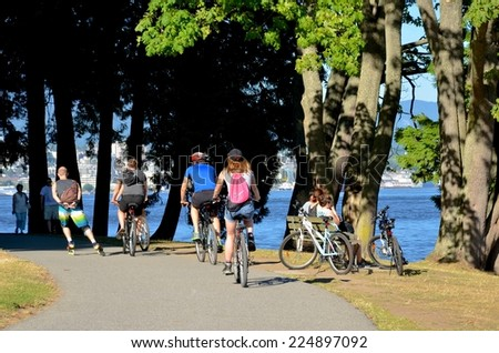 VANCOUVER - JULY 27: People at Stanley Park Seawall on July 27, 2014 in Vancouver Canada. Famous seawall where park visitors walk, bike, roll, and fish on the 22 kilometers seawall route. - stock photo