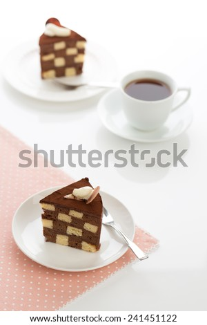 Vanilla and chocolate checkerboard cake makes a perfect tea time treat! The cake is garnished with whipped cream and cocoa powder, frosted with chocolate ganache. - stock photo