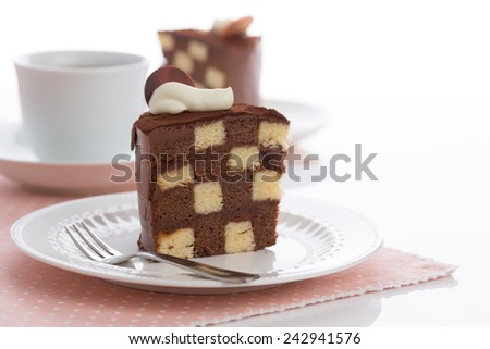 Vanilla and chocolate checkerboard cake makes a perfect tea time treat! The cake is garnished with whipped cream and cocoa powder, frosted with chocolate ganache. (With copy space.) - stock photo