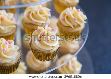 Vanilla bean mini cupcakes decorated with cyan and pink candy beads on a clear teared tray up close - stock photo