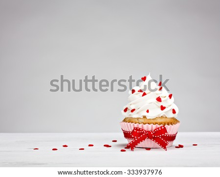 Vanilla Cupcake with buttercream icing, heart shaped sprinkles and a red bow.