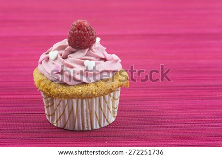 vanilla cupcake with pink frosting and sugar hearts in white and pink sprinkled on and fresh raspberry on top - stock photo