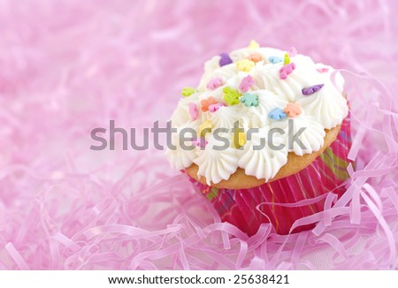Vanilla cupcake with sprinkles and pastel colors isolated on pink background closeup diagonal copy space - stock photo