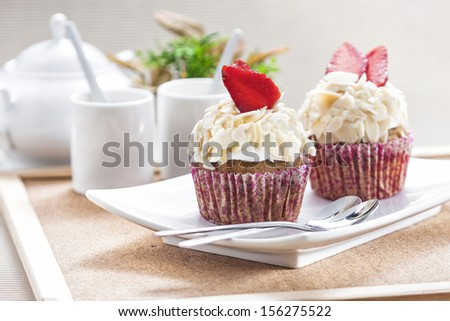 Vanilla cupcake with strawberry and almond against tea set in wooden frame background.