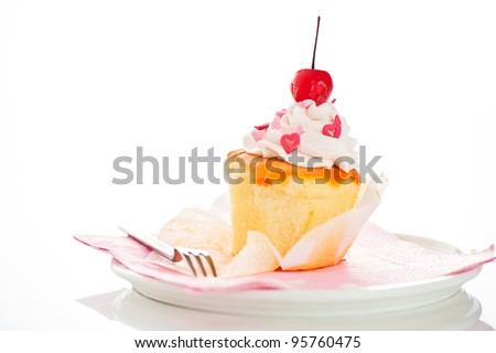 Vanilla cupcake with white cream heart as decoration and a cherry on the top on a white background as a studio shoot
