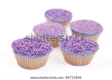 Vanilla cupcakes, decorated with lavender-coloured butter cream and pink & purple sprinkles - stock photo