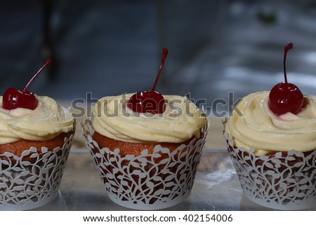Vanilla cupcakes with butter cream frosting and a cherry on top. Party celebration, calorie - stock photo