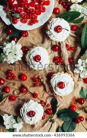 Vanilla cupcakes with  cream frosting and . Cherry cake Shot on wooden table  currant muffin   - stock photo