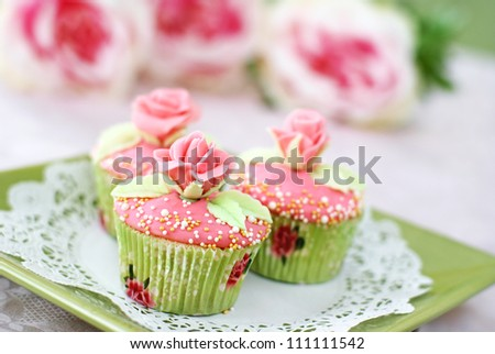 Vanilla cupcakes with pink frosting decorated with pearls and roses made of fondant. - stock photo