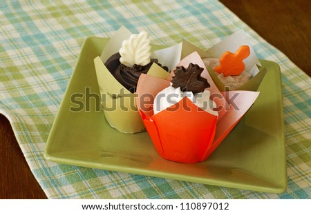 Vanilla cupcakes with vanilla, chocolate, and mocha frosting, decorated with chocolate leaves - stock photo