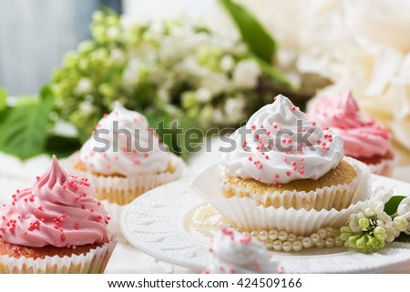 Vanilla cupcakes with white and pink cream on a white table,white flower and leaf, lilac, selective focus, close up - stock photo