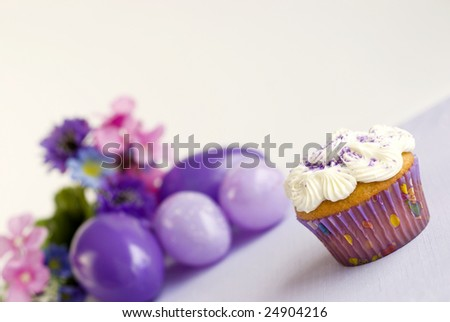 Vanilla Easter Cupcake with purple sugar sprinkles with selective focus, Easter eggs and flowers in background, slanted copy space - stock photo