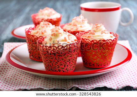 Vanilla frosting cupcakes with pink sprinkles and tea