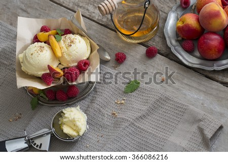 Vanilla ice cream ball with fresh peach and raspberry on rustic wooden table top. - stock photo