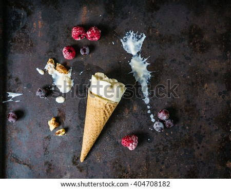 Vanilla ice cream in a waffle cone on a dark metal surface, frozen berries and nuts. Flat lay, copy space, top view. - stock photo