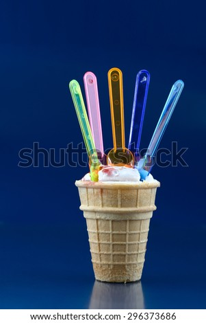 Vanilla ice cream in waffle cup and five spoons over blue - stock photo
