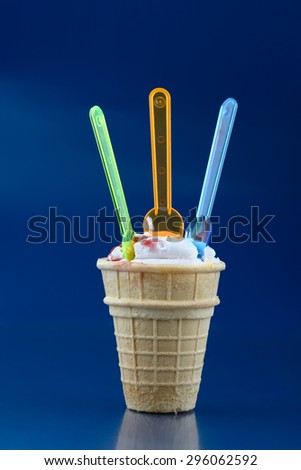 Vanilla ice cream in waffle cup and three spoons over blue - stock photo