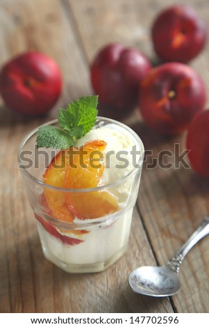 Vanilla ice cream with caramelized peaches - stock photo