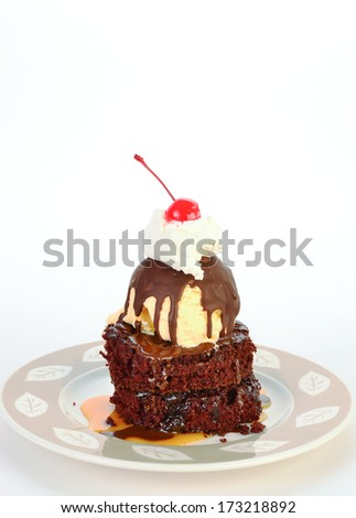 Vanilla Ice Cream with chocolate crust on layers of chocolate cake with caramel syrup and chocolate syrup topped with whipped cream and maraschino Cherry. - stock photo