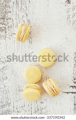 Vanilla macarons over a rustic wooden background with a retro tone. - stock photo