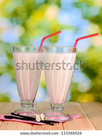 Vanilla milk shakes on wooden table on bright background