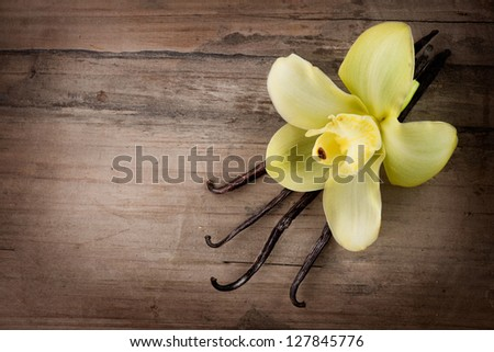 Vanilla Pods and Flower over Wooden Background. Vanilla Pod Stick - stock photo