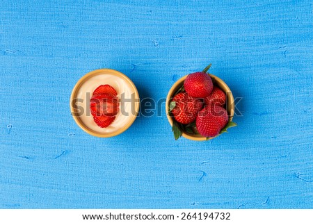 Vanilla pudding and strawberries in small  bowls on blue background. - stock photo