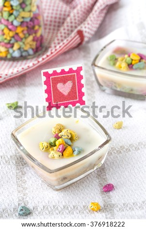 Vanilla pudding with pebble chocolates on red, white and gray kitchen towel, heart image attached, chocolate jar at the background standing on red and white napkin.  - stock photo