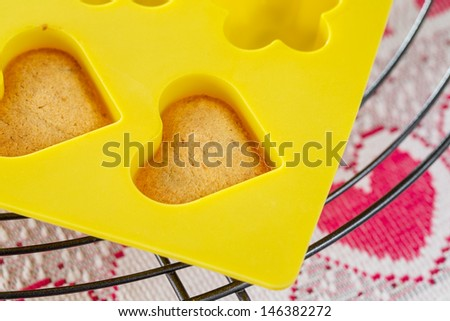 Vanilla  sponge cake hearts in yellow silicone mold, cooling on metal rack - stock photo