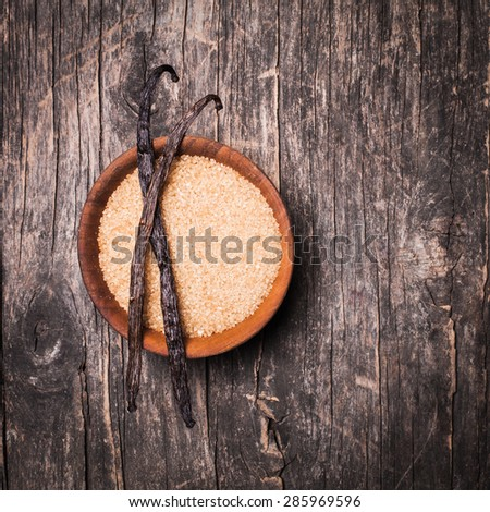 Vanilla sugar in a wooden bowl on a rustic background. Two vanilla pods on brown sugar - stock photo