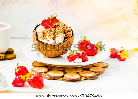 Vanilla vegan ice cream with peanut butter, buckwheat and strawberries on coconut cup. Marble background.Vegan or diet food concept.Sun light.