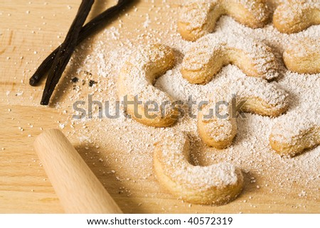vanillekipferl, an austrian pastry made for christmas, on wooden platter with vanilla pods and powdered sugar