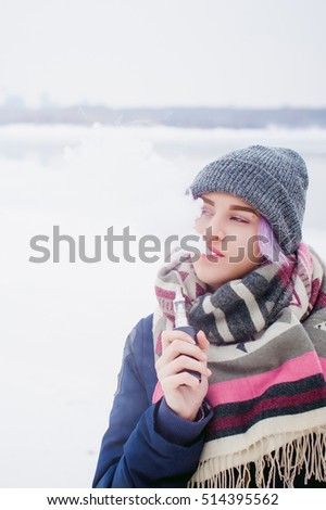 vaping girl. winter street portrait of a woman hipster, purple-dyed hair, a gray knitted hat and scarf. woman smokes an electronic cigarette in the street near the snow-covered river
