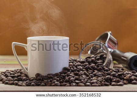 Vapor on coffee cup with beans background - stock photo