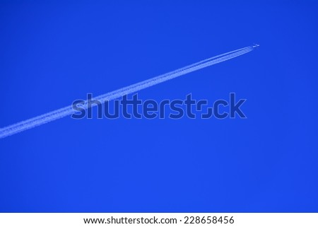 Vapor trail- A plane flying on a perfectly blue sky - stock photo