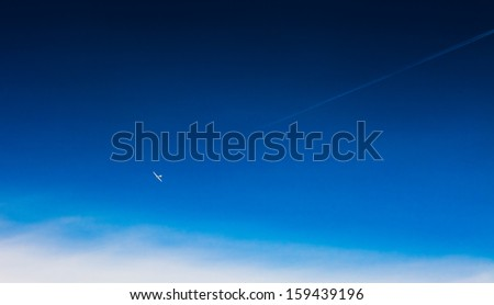 Vapor trail from an airplane in the blue sky, the moon and the plane; light single-engine plane - stock photo