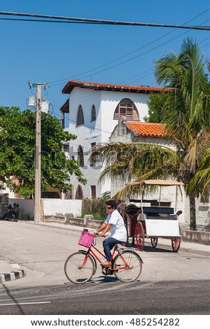 VARADERO, CUBA - February 08, 2008. Woman rides a bicycle on a street in Varadero town.