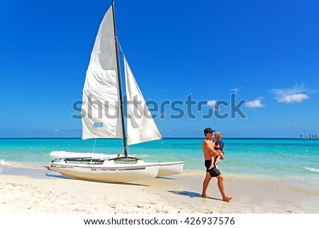 VARADERO, CUBA - May 10, 2016: Father and daughter walking on a beach with boat and beautiful ocean. Cuba is considered one of the safest tourist destinations - stock photo