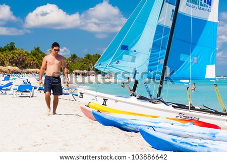 VARADERO,CUBA-MAY 27:Tourist walking along the beach May 27,2012 in Varadero.With over a million visitors per year,Varadero is the most important destination for the growing cuban tourism industry - stock photo