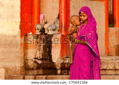 VARANASI, INDIA - APRIL 24: Unidentified hindu woman with her child watching the ritual bath in the river Ganga on April 24, 2011 in Varanasi, India. The holy ritual bath is held every day.