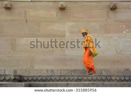 VARANASI, INDIA - AUG 23, 2015. Shaiva sadhu seeking alms on the street in Varanasi, India. Varanasi is a city dating to the 11th century B.C.E, the spiritual capital of India. - stock photo