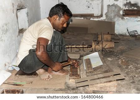 VARANASI, INDIA - CIRCA FEBRUARY 2011: Man punches manually holes in carton guide for Jacquard weaving looms. - stock photo