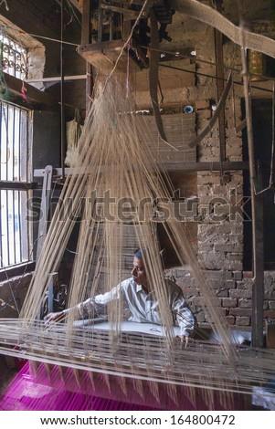 VARANASI, INDIA - CIRCA FEBRUARY 2011: Man weaving with an ancient Jacquard weaving machine, also called hand loom. - stock photo